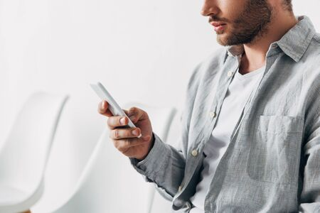 Cropped view of employee using smartphone in office Фото со стока