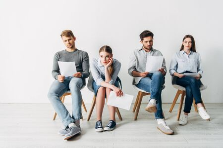 Group of employees with resume waiting for job interview in office