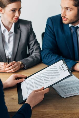 Selective focus of employee holding resume near skeptical recruiters looking at each other at table