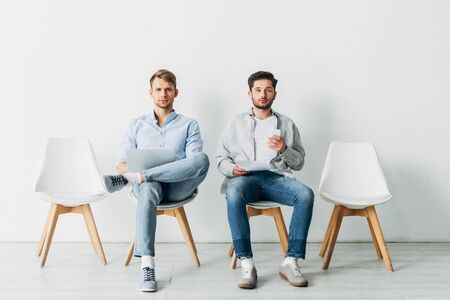 Employees with gadgets and resume looking at camera while waiting for job interview Фото со стока