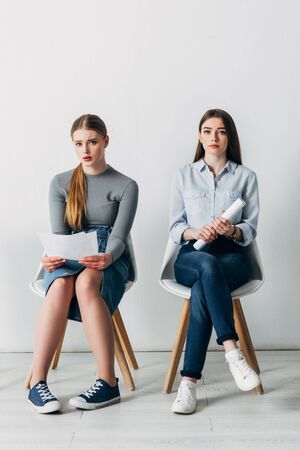 Attractive employees with resume looking at camera on chairs in office