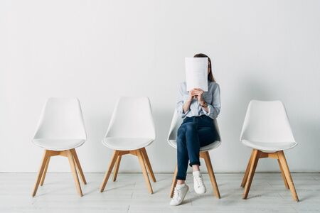 Young woman covering face with resume while waiting for job interview in office Фото со стока