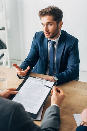 Selective focus of employee in suit looking at recruiter with resume at table