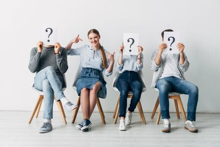 Cheerful girl pointing on oneself near employees holding cards with question marks in office Фото со стока