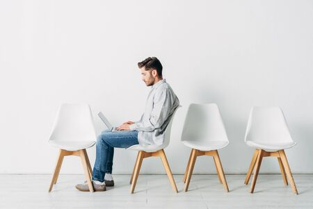 Side view of candidate using laptop on chair in office