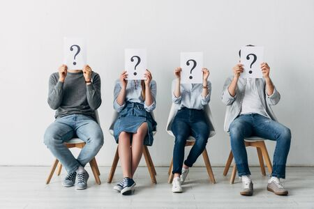 Young people holding cards with question marks while waiting for job interview in office Фото со стока