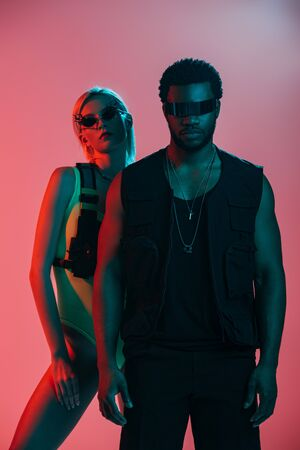 beautiful interracial couple posing in futuristic look and sunglasses on pink