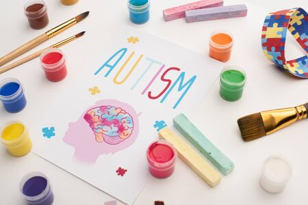 card with autism word and painting of head with brain on white with paint brushes, chalks and paints