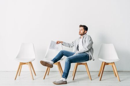 Side view of man with resume sitting on chair in office