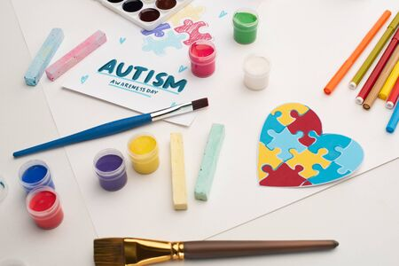card with Autism Awareness Day lettering and painting of puzzle on white with paint brushes, chalks, markers and puzzle heart