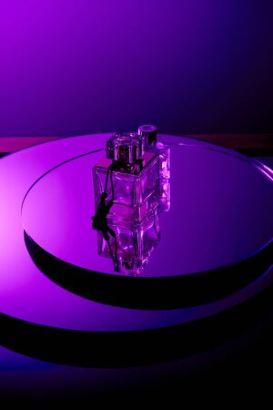 Violet perfume bottles on round mirror surface isolated on purple