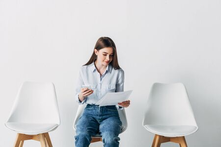 Beautiful woman using smartphone and holding resume on chair in office Reklamní fotografie
