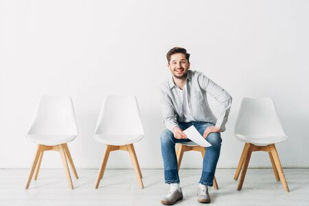 Smiling man with resume looking at camera while sitting on chair in office Фото со стока
