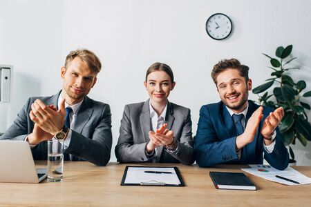 Smiling recruiters clapping and looking at camera near documents and laptop on table
