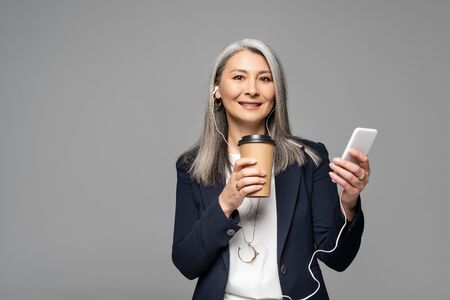 emotional asian businesswoman with coffee to go listening music with earphones and smartphone isolated on grey