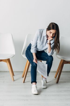 Pensive woman looking at resume while waiting for job interview in office