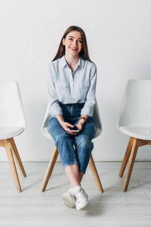 Smiling employee holding smartphone with blank screen on chair in office
