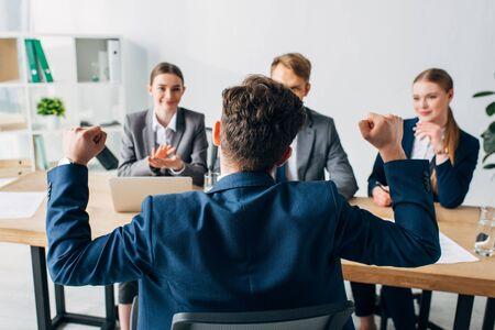 Selective focus of employee showing yes gesture near smiling recruiters in office Фото со стока