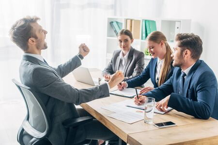 Side view of smiling employee showing yeah gesture near recruiters at table Фото со стока