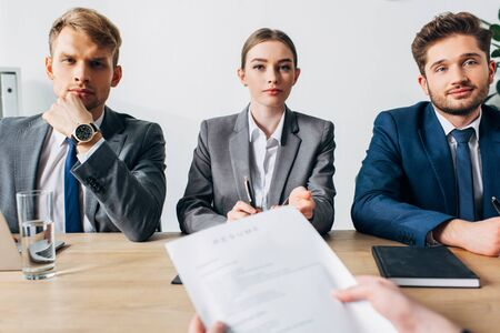 Selective focus of recruiters looking at camera near employee holding resume at table