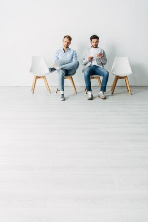 Handsome employees with resume and laptop sitting on chairs in office