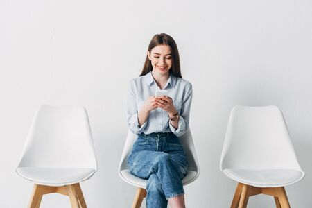 Smiling employee using smartphone while waiting for job interview in office