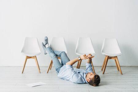 Employee using smartphone while lying on floor near resume in office Фото со стока