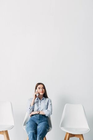 Beautiful young woman talking on smartphone while waiting job interview in office