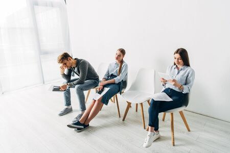 Tired man and women waiting for job interview in office Фото со стока