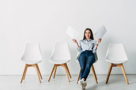 Smiling woman holding resume and smiling at camera on chair in office