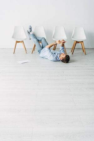 Low angle view of man using smartphone on floor while waiting for job interview Фото со стока