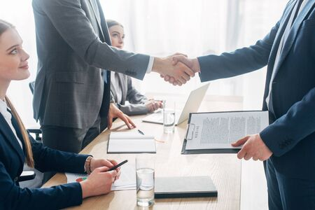 Side view of employee with resume shaking hands with recruiter during job interview in office Фото со стока