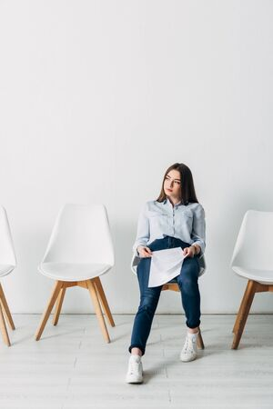 Attractive applicant holding resume on chair in office