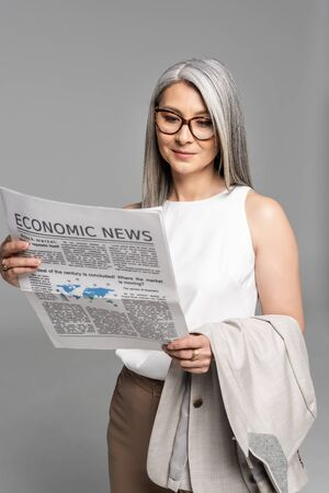 smiling asian businesswoman in eyeglasses reading business newspaper isolated on grey