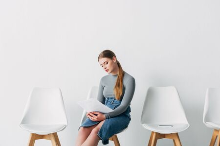 Attractive woman holding resume while waiting for job interview in office