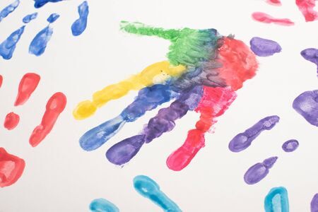 top view of colorful hand prints on white for World Autism Awareness Day