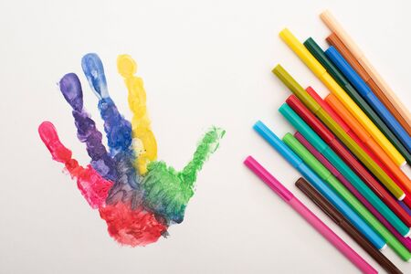 top view of colorful handprint and flat pens on white for World Autism Awareness Day