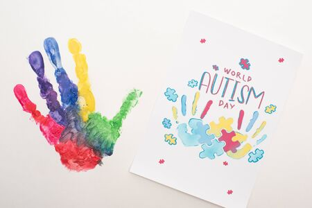 top view of colorful handprint and card with puzzle and World Autism Day lettering on white Banque d'images