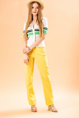 stylish girl posing in yellow trousers, polo and straw hat on beige