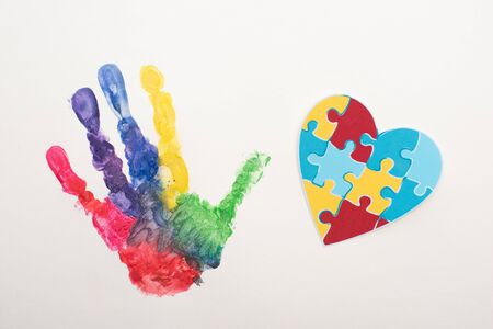 top view of colorful handprint and puzzle heart on white for World Autism Awareness Day