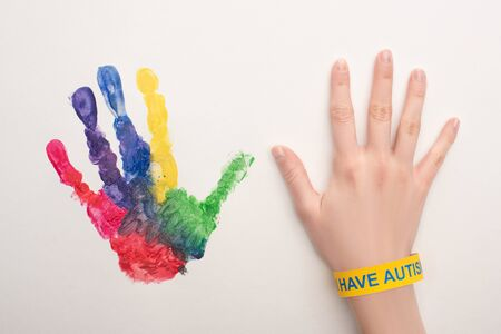 cropped view of female hand with autism bracelet on white with colorful handprint Banque d'images