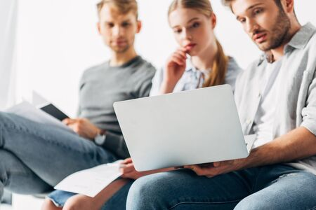 Selective focus of employees looking at laptop while waiting for job interview