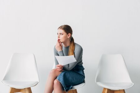 Pensive candidate holding resume while waiting job interview in office
