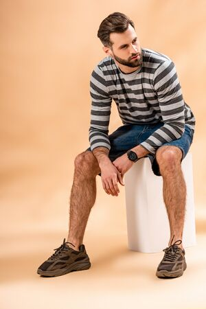 bearded man in striped sweatshirt sitting on white cube on beige