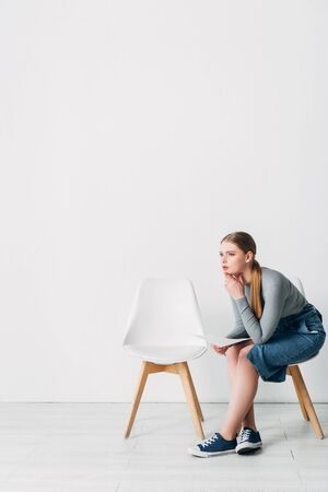 Side view of woman with resume looking away on chair in office