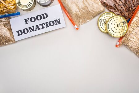 top view of cans and groats in zipper bags near card with food donation lettering on white background