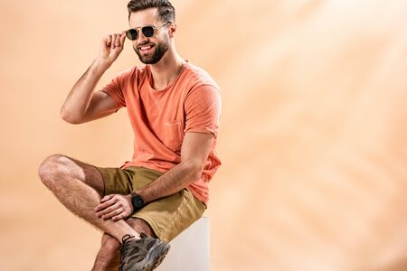 cheerful young man in shorts, summer t-shirt and sunglasses sitting on white cube on beige