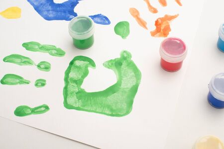 close up of colorful handprints and paints on white for World Autism Awareness Day