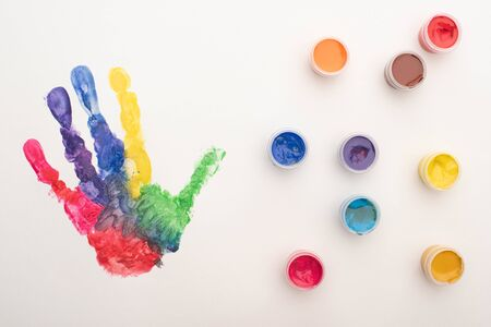 top view of colorful handprint and paints on white for World Autism Awareness Day