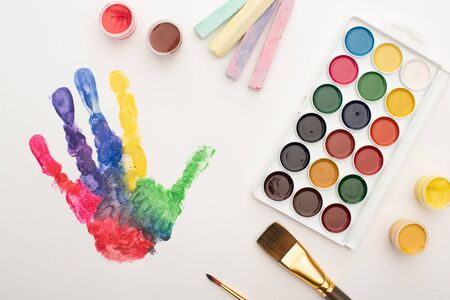 top view of colorful handprint, chalks, paint brushes and paints on white for World Autism Awareness Day Archivio Fotografico